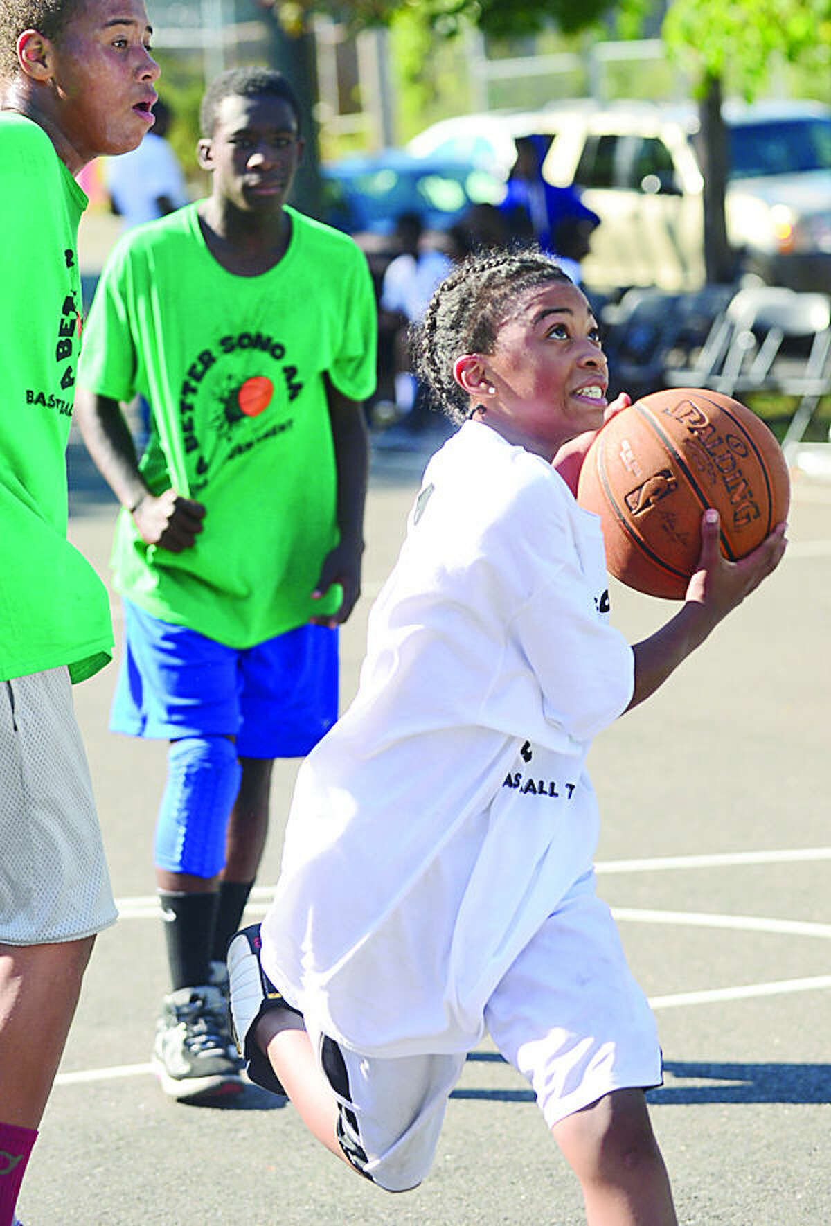 Hour photo / Erik Trautmann 14 year old Robert Raphael goes to the hoop in the basketball tournament during the 3rd annual South Norwalk Community Day Saturday at Ryan Park.