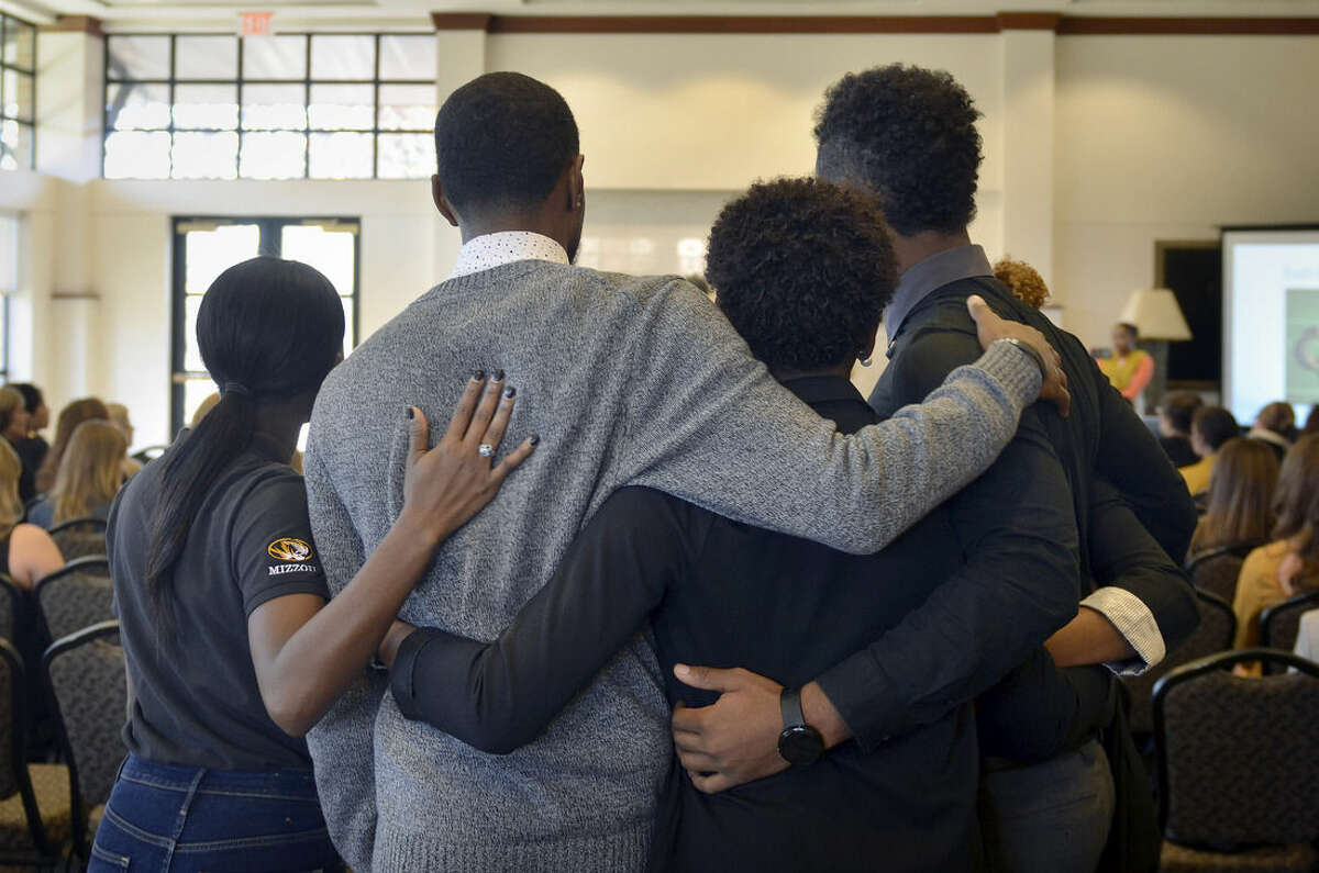 In this Saturday, Nov. 7, 2015, photo, members of the anti-racism and black awareness group Concerned Student 1950 embrace during a protest in the Reynolds Alumni Center on the University of Missouri campus in Columbia, Mo. Some campus groups have been protesting the way university president Tim Wolfe has dealt with issues of racial harassment during the school year. Jonathan Butler, a black graduate student, is in the sixth day of a hunger strike to call attention to the issue. Missouri football players announced Saturday night on Twitter that they will not participate in team activities until the university president is removed from office. (Ellise Verheyen/Missourian via AP) MANDATORY CREDIT