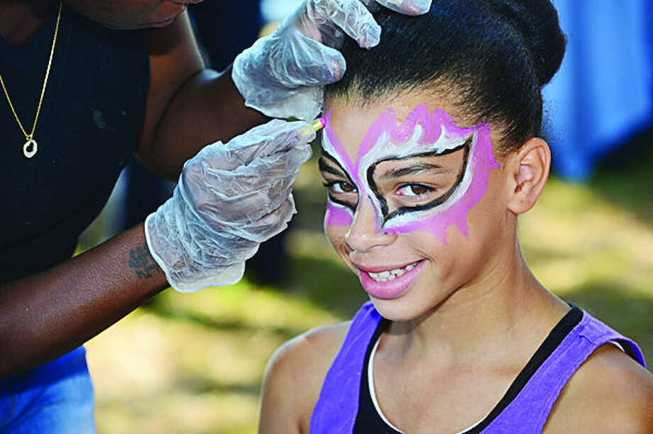 Hour photo / Erik Trautmann 12 year old Hyana Goigo gets herface painted during the 3rd annual South Norwalk Community Day Saturday at Ryan Park.