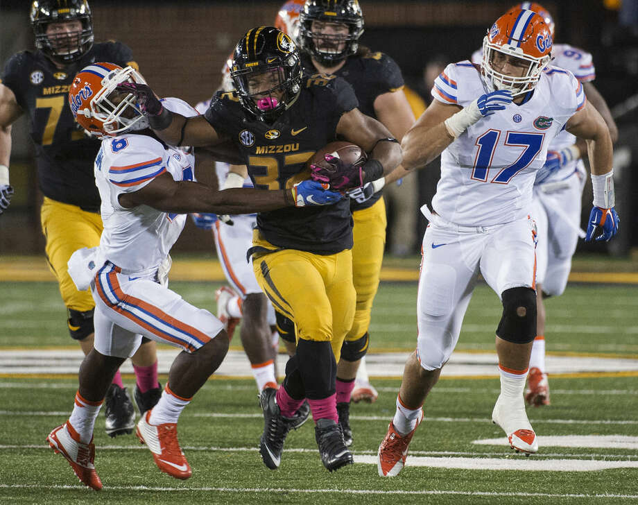 FILE - In this Oct. 10, 2015, file photo, Missouri running back Russell Hansbrough, center, fights his way past Florida's Nick Washington, left, and Jordan Sherit, right, during an NCAA college football game in Columbia, Mo. Some Missouri football players announced Saturday night, Nov. 7, 2015, on Twitter that they will not participate in team activities until the university president, Tim Wolfe, is removed from office. The statement from the athletes of color was tweeted out Saturday by several members of the football team, including Hansbrough. (AP Photo/L.G. Patterson. File)