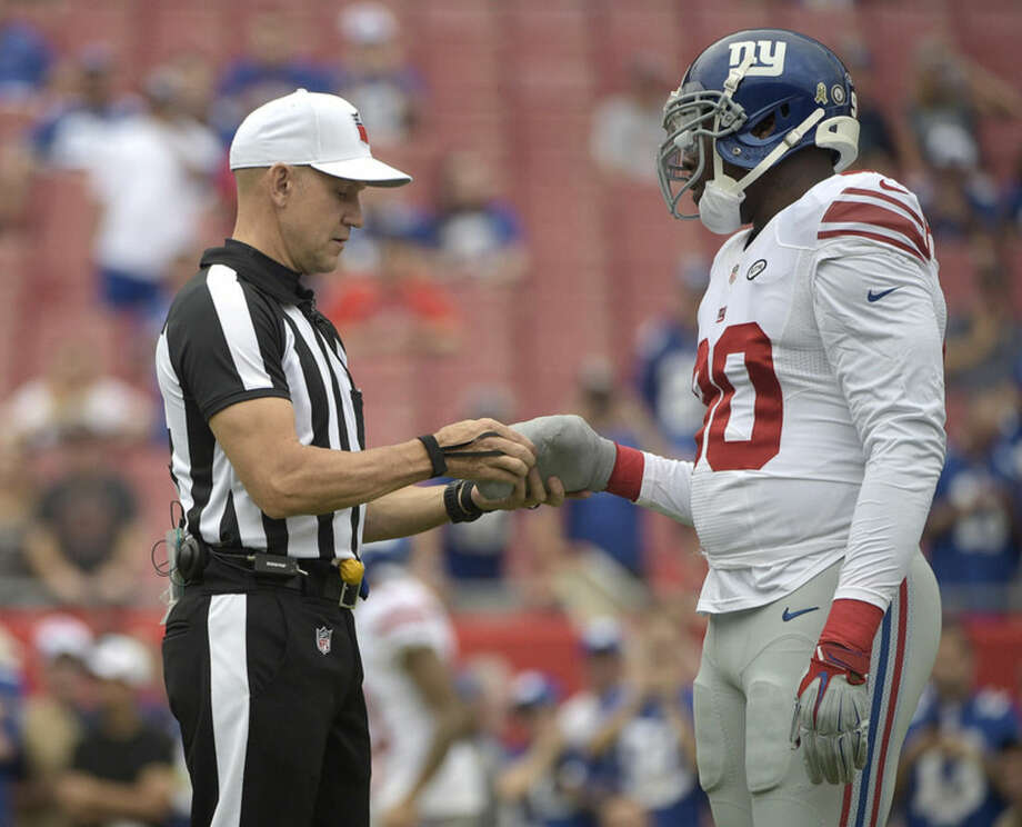 NFL referee Clete Blakeman, check's the bandage on New York Giants defensive end Jason Pierre-Paul's hand before an NFL football game against the Tampa Bay Buccaneers Sunday, Nov. 8, 2015, in Tampa, Fla. Pierre-Paul is playing in his first game since injuring his hand with fireworks during the off-season. (AP Photo/Phelan M. Ebenhack)