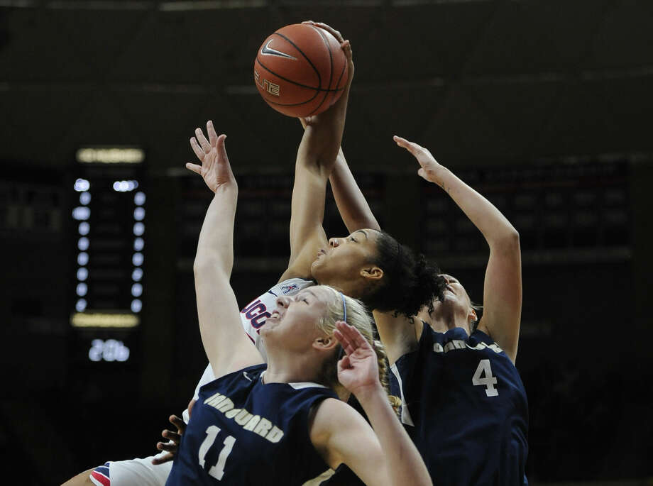 Connecticut's Gabby Williams, center, pulls down a rebound against Vanguard's Jaime Goff, left, and Melissa Norman, right, during the first half of an NCAA college exhibition basketball game Sunday, Nov. 8, 2015, in Storrs, Conn. (AP Photo/Jessica Hill)