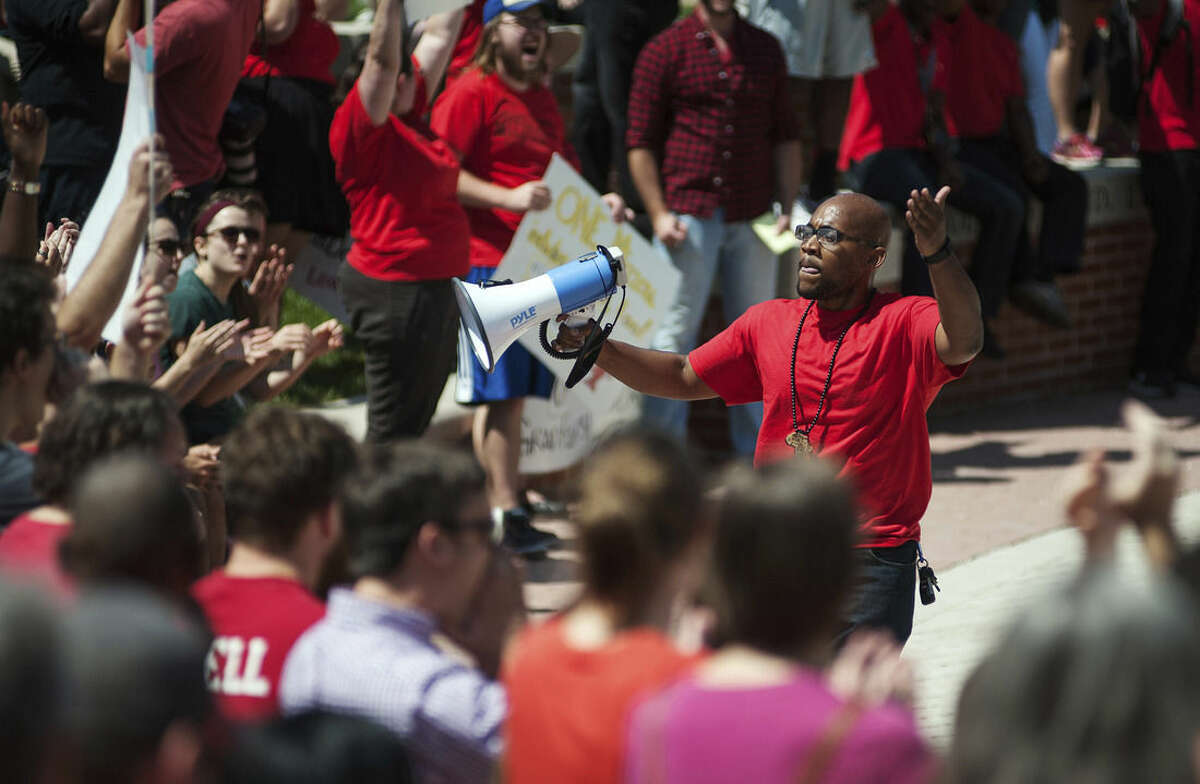 In this Aug. 26, 2015 photo, Jonathan Butler uses a megaphone to encourage others to stand and chant during a