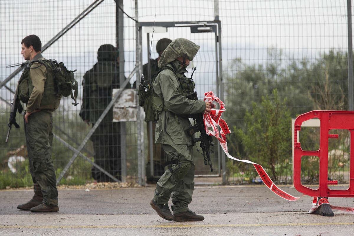 Israeli soldiers clear a road after a Palestinian woman was shoot dead after she drew a knife in check point near the West Bank Palestinian town of Qalqilya, Monday, Nov. 9, 2015. Defense Ministry spokeswoman Arielle Heffez says the woman ignored warning shots and calls to stop as she approached the post. (AP Photo/Ariel Schalit)