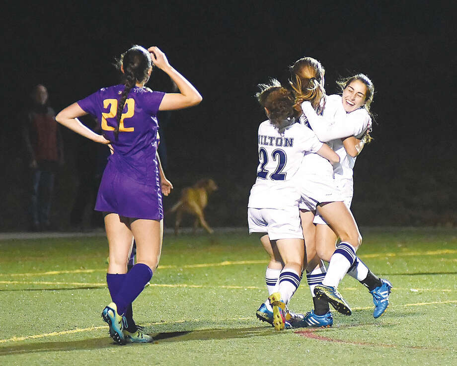 Hour photo/John Nash Wilton High's Rebecca Hersch (22 in white) and Zoe Lash, far right, embrace teammate Ally Dejana as Westhill's Erica Shaulson looks on after Dejana scored the only goal in the Warriors 1-0 first round state tournament win at Kristine Lilly Field on Monday. The freshman's tally came in 10:30 left in the game, sending Wilton into the second round.