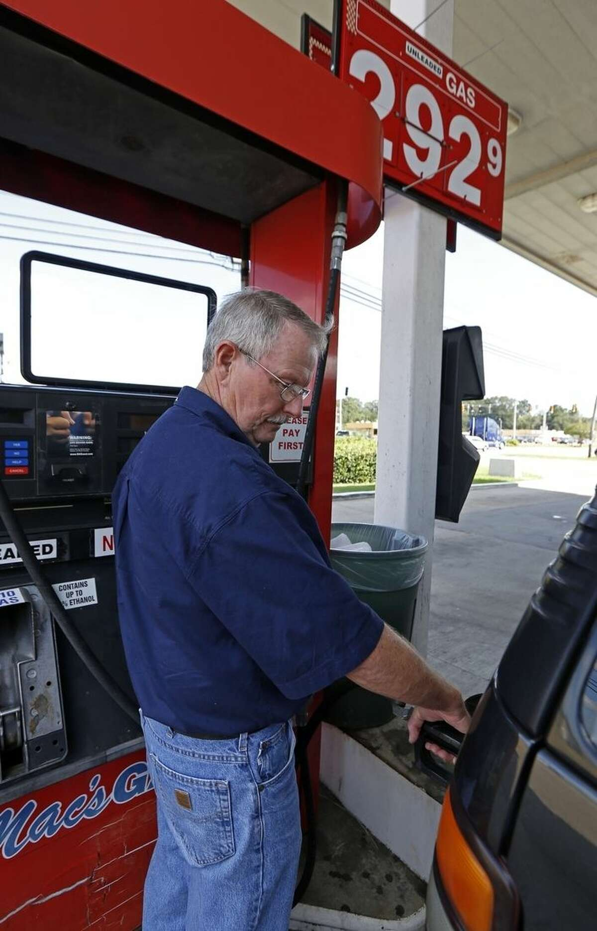 In this Wednesday, Sept. 24, 2014 photo, Foster Gilley, of Chatom, Ala., fills his SUV's tank with $2.92-per-gallon regular gas at Mac's Gas in Richland, Miss. The typical autumn decline in gasoline prices is getting a big push lower by falling global oil prices. By the end of the year, up to 30 states could have an average gasoline price of under $3 a gallon. Gilley and his wife were visiting his brother in Vicksburg and were
