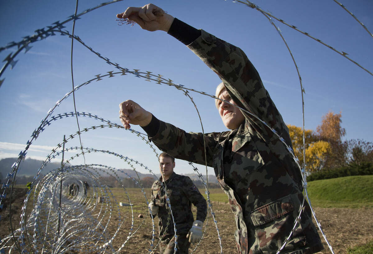A Slovenian soldier works on the newly erected razor-wired fence on the Croatian border in Gibina, Slovenia, Wednesday, Nov. 11, 2015. Slovenia has started erecting a barbed-wire fence on the border with Croatia to prevent uncontrolled entry of migrants into the already overwhelmed alpine state. (AP Photo/Darko Bandic)