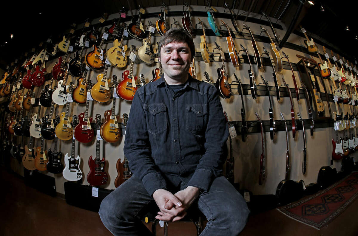 Brian Douglas is photographed at the Cream City Music store Wednesday, Nov. 11, 2015, in Brookfield, Wis. Cream City Music sells more than 1,800 items from guitar picks to vintage instruments on Reverb.com, a musical equipment marketplace. The retailer began selling on Reverb.com two years ago. Small retailers use high-tech innovations to build relationships with customers; they often can't compete with big chains on prices, so they aim at better, individualized service. (AP Photo/Morry Gash)