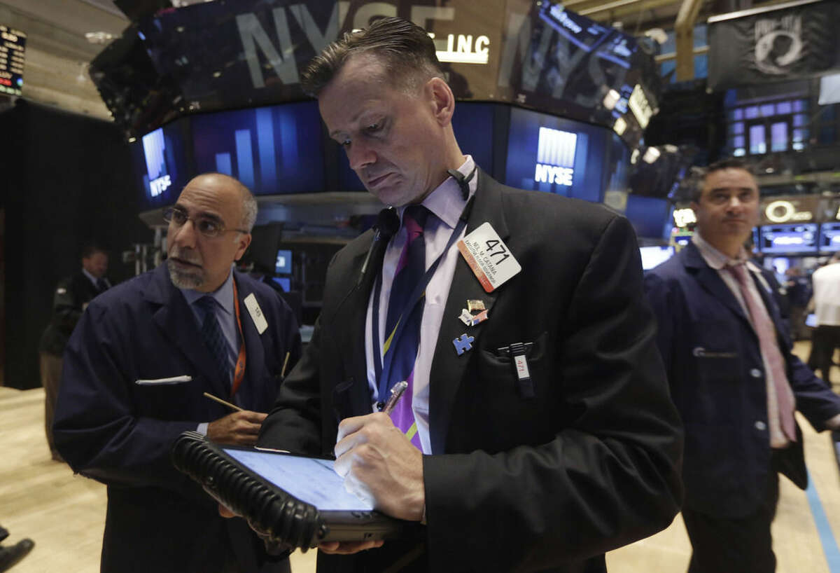Neil Catania, center, works with fellow traders on the floor of the New York Stock Exchange, Thursday, Oct. 2, 2014. U.S. markets were mostly flat in early trading Thursday, follow a sell-off the day before, as U.S. investors had little reaction to comments from European Central Bank President Mario Draghi, who announced new economic stimulus measures for the continent. (AP Photo/Richard Drew)