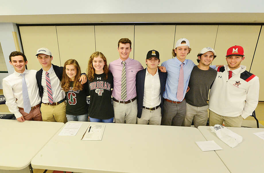 Hour photo/Erik Trautmann Staples High School seniors from the left, Ben Schwaeber, Michael Reale, Hannah DeBalsi, Mia Bullock, Sam Ahlgrim, Ross Goldberg, Connor Chamberlin, Josh Willis and Nate Panzer sign national letters of intent to play for various universities during a ceremony Wednesday at the school.