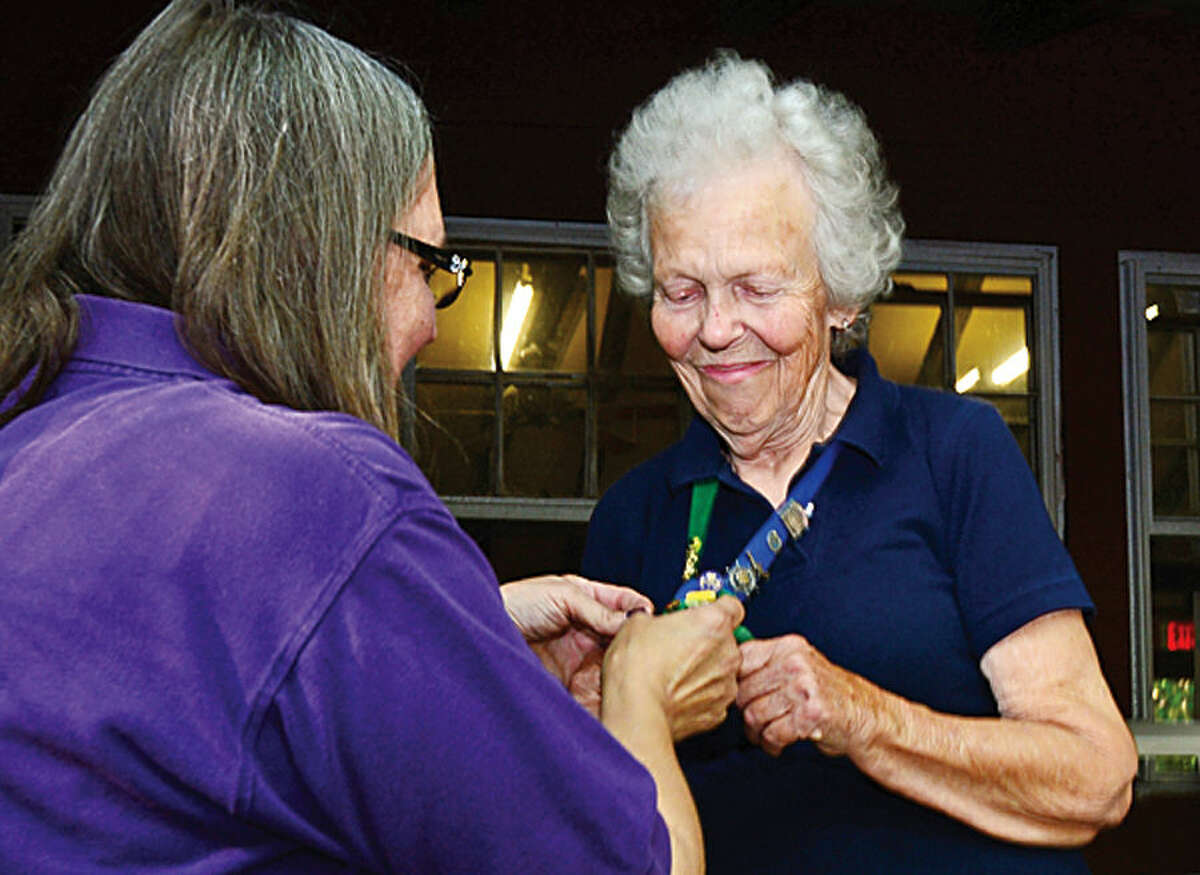 Hour photo / Erik Trautmann Courtenay Austin receives her 75 year pin from a fellow troop leader during a tribute ceremony for Austin in honor of her 75th year in the Girl Scouts Saturday at Camp Aspetuck.