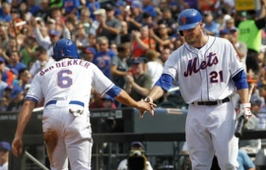 New York Mets' Matt den Dekker (6) is congratulated by Lucas Duda (21) after scoring on a sacrifice fly by Daniel Murphy during the first inning against the Houston Astros in an interleague baseball game Sunday, Sept. 28, 2014, in New York. (AP Photo/Rich Schultz)
