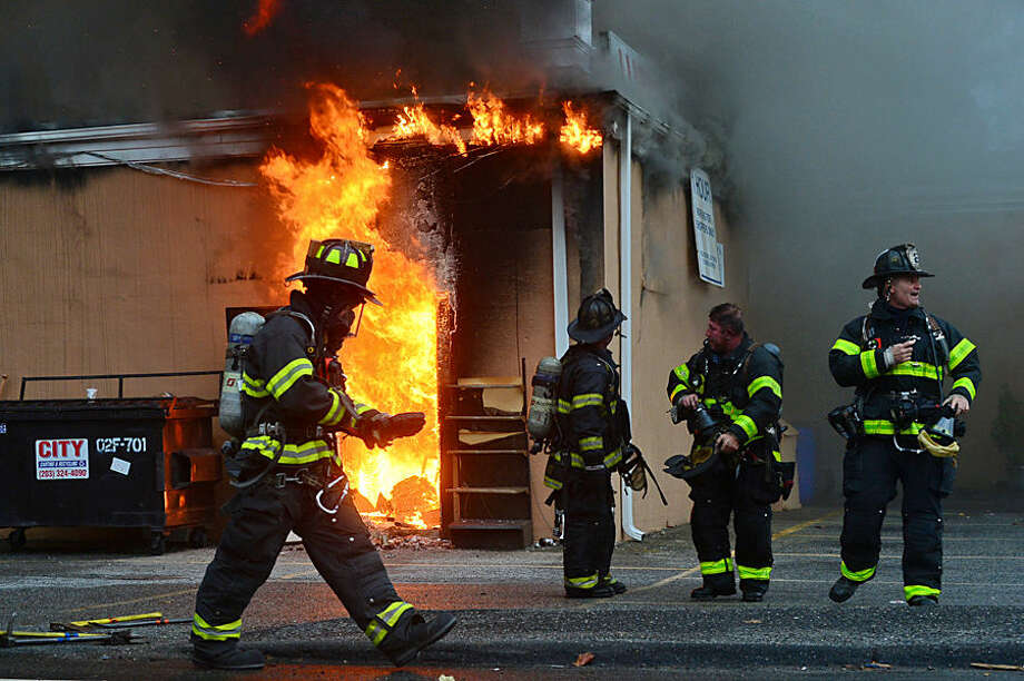 Hour photo / Erik Trautmann Norwalk firefighters battle a blaze at the Ludlow Shopping Center Thursday afternoon.