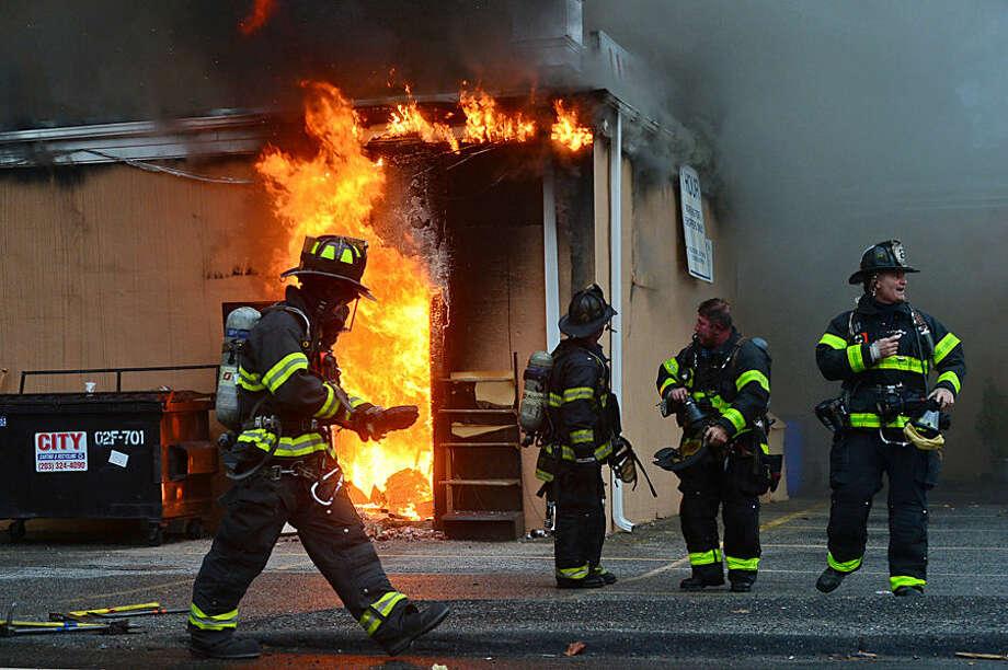 Hour photo / Erik Trautmann Norwalk firefighters battle a blaze at the Ludlow Shopping Center Thursday afternoon.