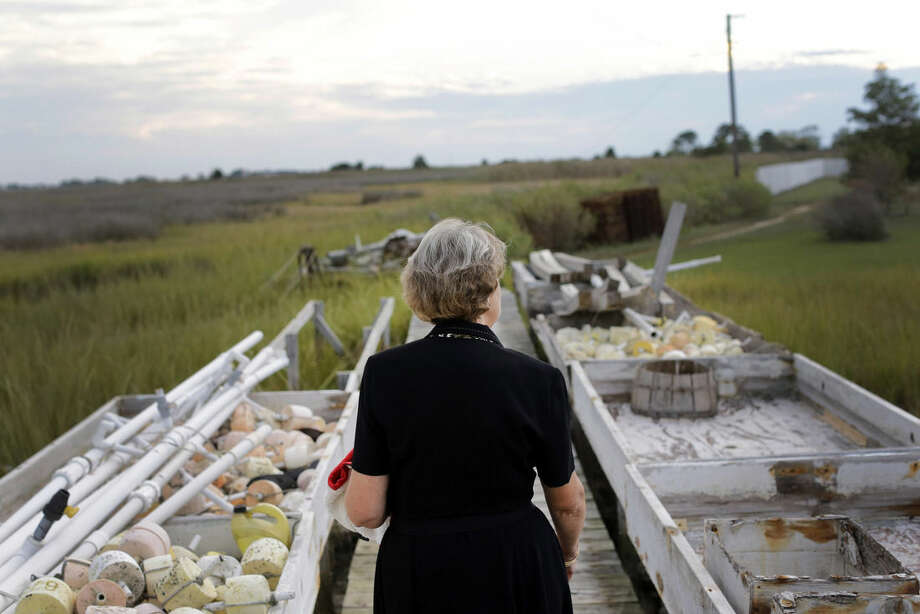 """In this photo taken Sept. 23, 2014, Jennifer Dize walks on a dock behind her home on Smith Island, Md. Dize is asking the U.S. Supreme Court to take up her late husband's case after he got sick and sued his employer, the Association of Maryland Pilots, in 2008, claiming a boat maintenance project led to a deadly respiratory illness. However, his bosses said his work didn't qualify him to be a """"seaman"""" entitled to sue his employer under a federal law. """"I would like him to be recognized as a good seaman,"""" she said of her husband. """"Because he was."""" (AP Photo/Patrick Semansky)"""
