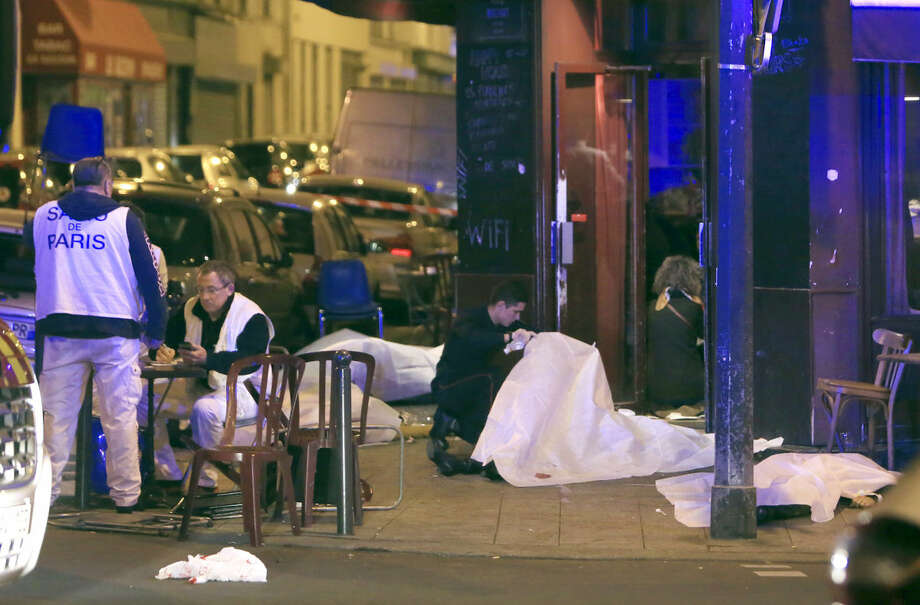 Victims lay on the pavement outsidde a Paris restaurant, Friday, Nov. 13, 2015. Police officials in France on Friday report multiple terror incidents, leaving many dead. It was unclear at this stage if the events are linked. (AP Photo/Thibault Camus)