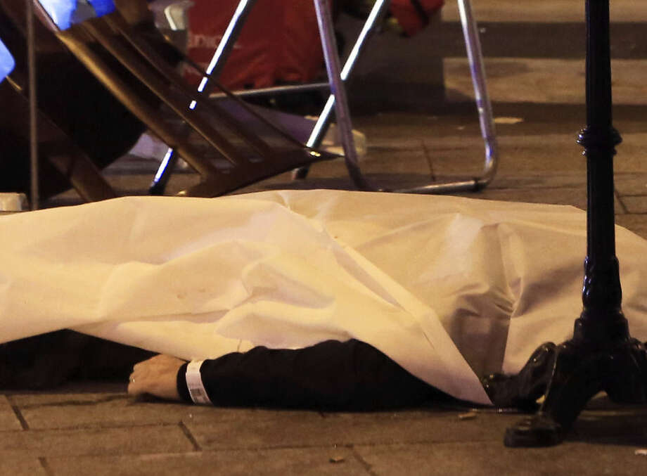 RETRANSMISSION FOR ALTERNATIVE CROP - A victim is pictured on the pavement outside a Paris restaurant, Friday, Nov. 13, 2015. Police officials in France on Friday report multiple terror incidents, including shootings, explosions and hostage taking, leaving many dead. (AP Photo/Thibault Camus)