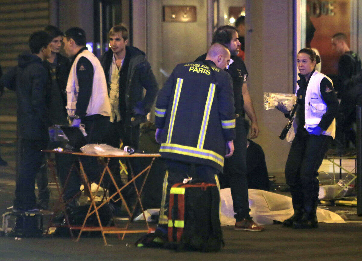 RETRANSMISSION FOR ALTERNATIVE CROP - Rescue workers at the scene as victims lay on the pavement outside a Paris restaurant, Friday, Nov. 13, 2015. Police officials in France on Friday report multiple terror incidents, leaving many dead. It was unclear at this stage if the events are linked. (AP Photo/Thibault Camus)
