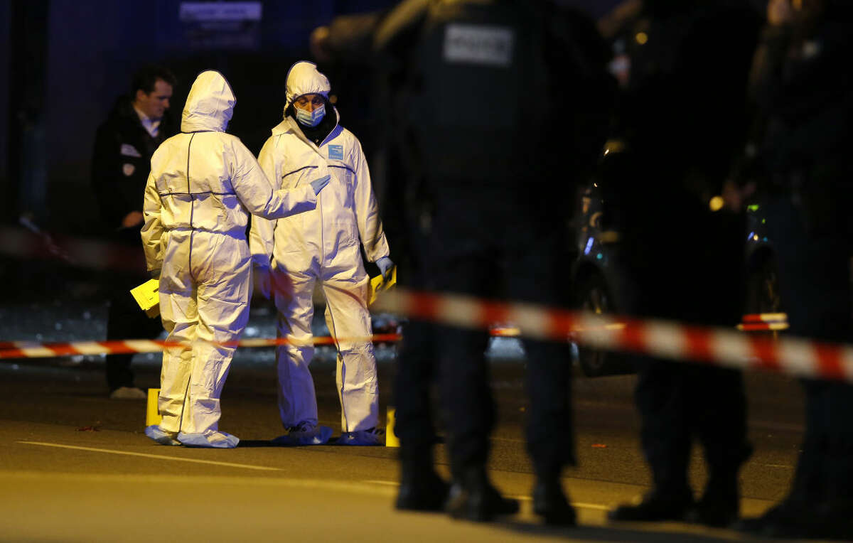 Investigating police officers work outside the Stade de France stadium after an international friendly soccer match France against Germany, in Saint Denis, outside Paris, Friday Nov. 13, 2015. Several dozen people were killed in attacks around Paris on Friday, French President Francois Hollande said, announcing that he was closing the country's borders and declaring a state of emergency. (AP Photo/Michel Euler)