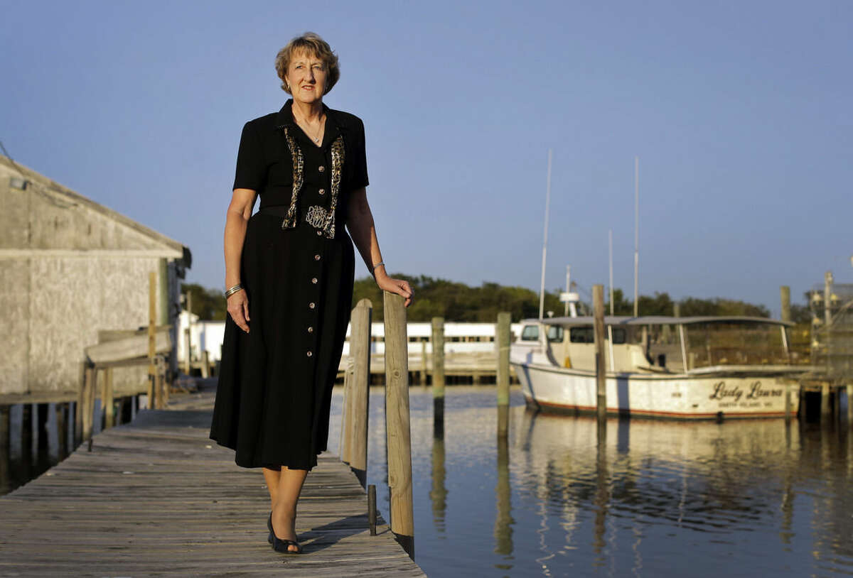 In this photo taken Sept. 23, 2014, Jennifer Dize poses on a dock behind her home on Smith Island, Md. Dize is asking the U.S. Supreme Court to take up her late husband's case after he got sick and sued his employer, the Association of Maryland Pilots, in 2008, claiming a boat maintenance project led to a deadly respiratory illness. However, his bosses said his work didn't qualify him to be a