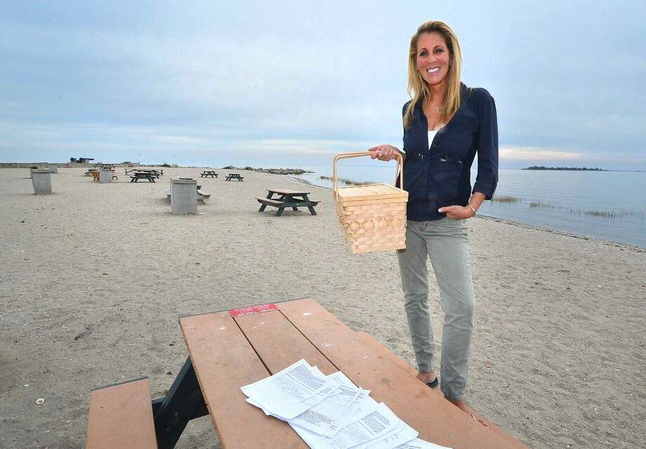 Hour Photo/Alex von Kleydorff Donna Chapman uses a picnic basket to carry her paperwork and signed petitions to Compo Beach, as she tries to preserve the layout of the beach property from potential change