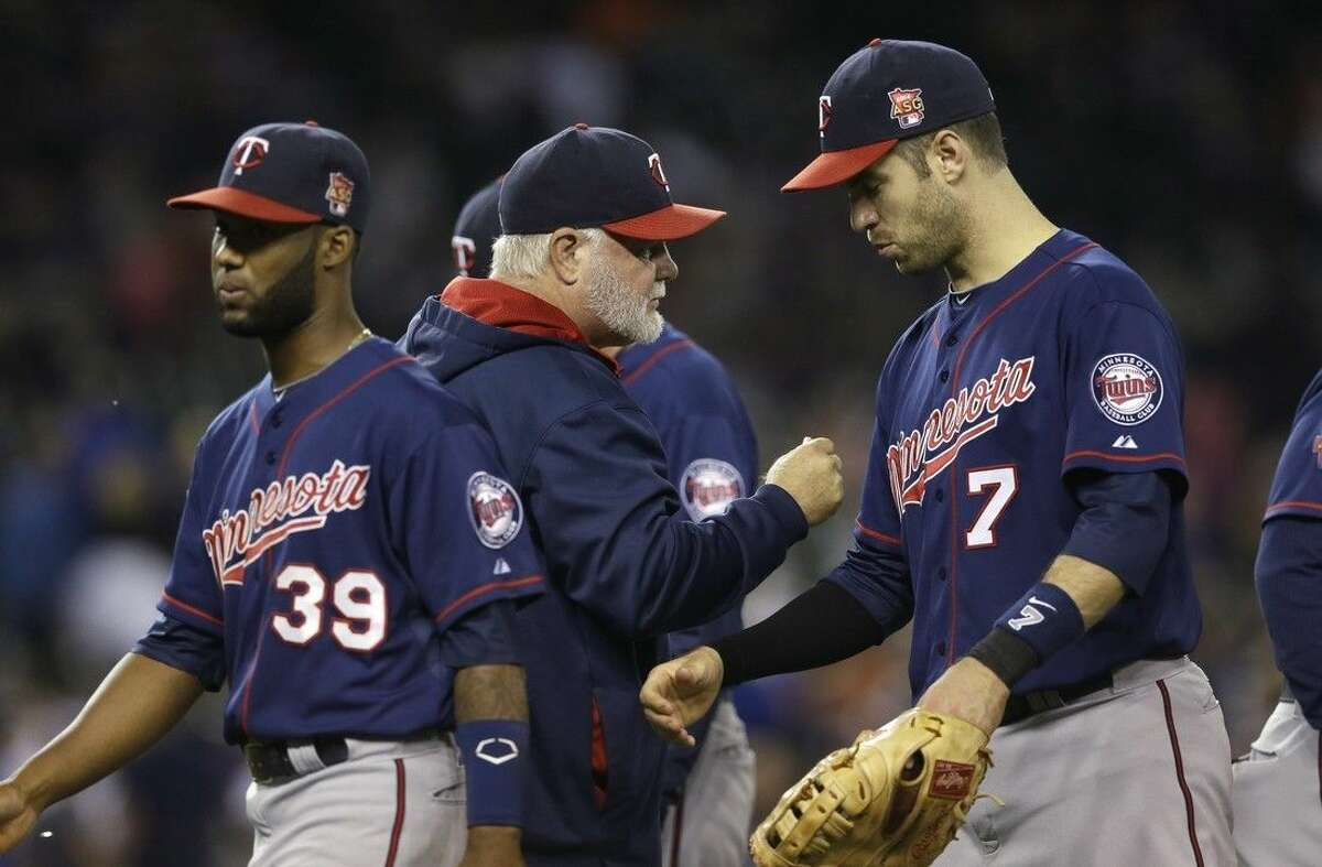 Minnesota Twins manager Ron Gardenhire, center, greets shortstop Danny Santana (39) and first baseman Joe Mauer (7) after their 12-3 win over the Detroit Tigers in a baseball game in Detroit, Saturday, Sept. 27, 2014. (AP Photo/Carlos Osorio)