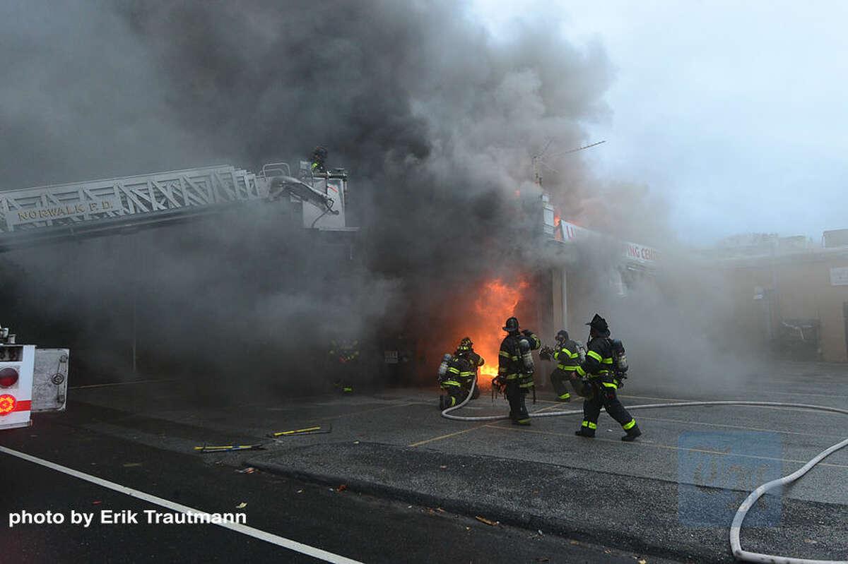 Hour photo / Erik Trautmann Norwalk firefighters battle a blaze that engulfed Ludlow Shopping Center in East Norwalk Thursday afternoon.