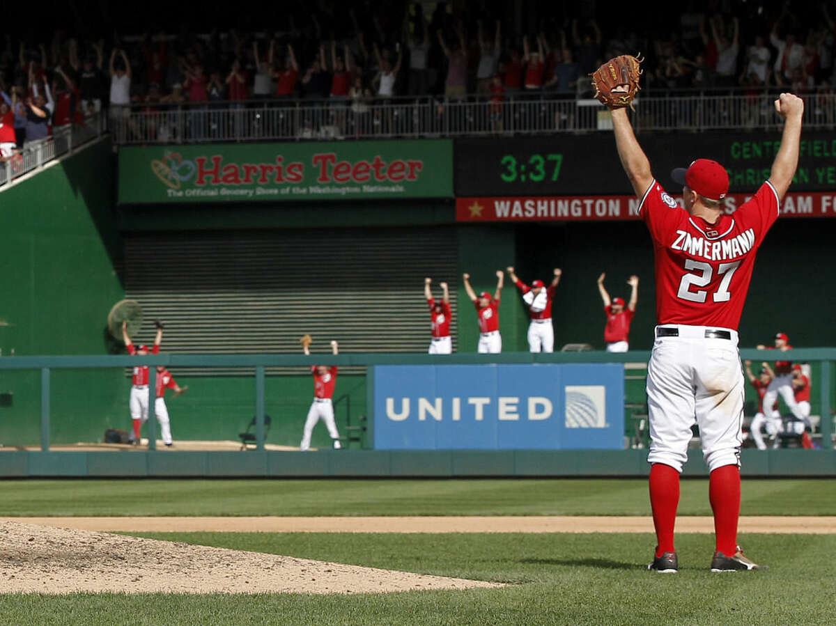 Washington Nationals starting pitcher Jordan Zimmermann (27) celebrates, as do players in the bullpen, after the last out in Zimmermann's no-hitter in a baseball game against the Miami Marlins at Nationals Park, Sunday, Sept. 28, 2014, in Washington. The Nationals won 1-0. (AP Photo/Alex Brandon)