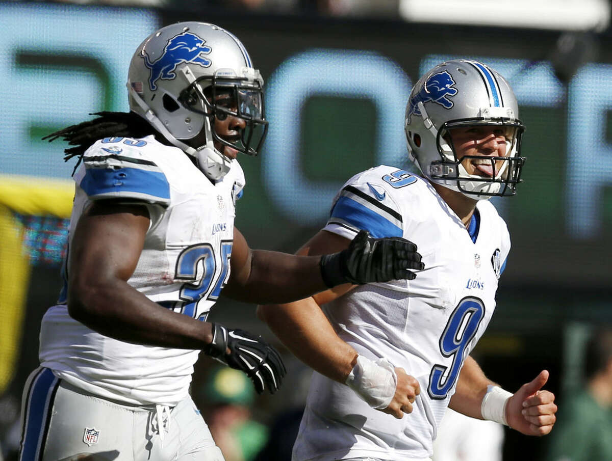 Detroit Lions quarterback Matthew Stafford (9) and running back Joique Bell (35) run off the field after Stafford scored on a touchdown run against the New York Jets during the second half of an NFL football game, Sunday, Sept. 28, 2014, in East Rutherford, N.J. (AP Photo/Kathy Willens)