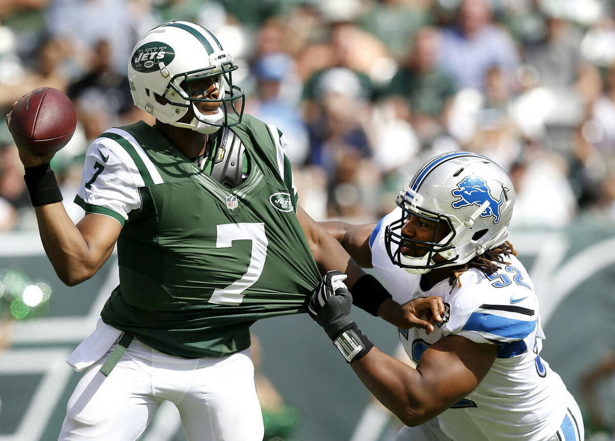 Detroit Lions defensive end Darryl Tapp, right, tugs at the jersey of New York Jets quarterback Geno Smith during the first half of an NFL football game, Sunday, Sept. 28, 2014, in East Rutherford, N.J. (AP Photo/Kathy Willens)