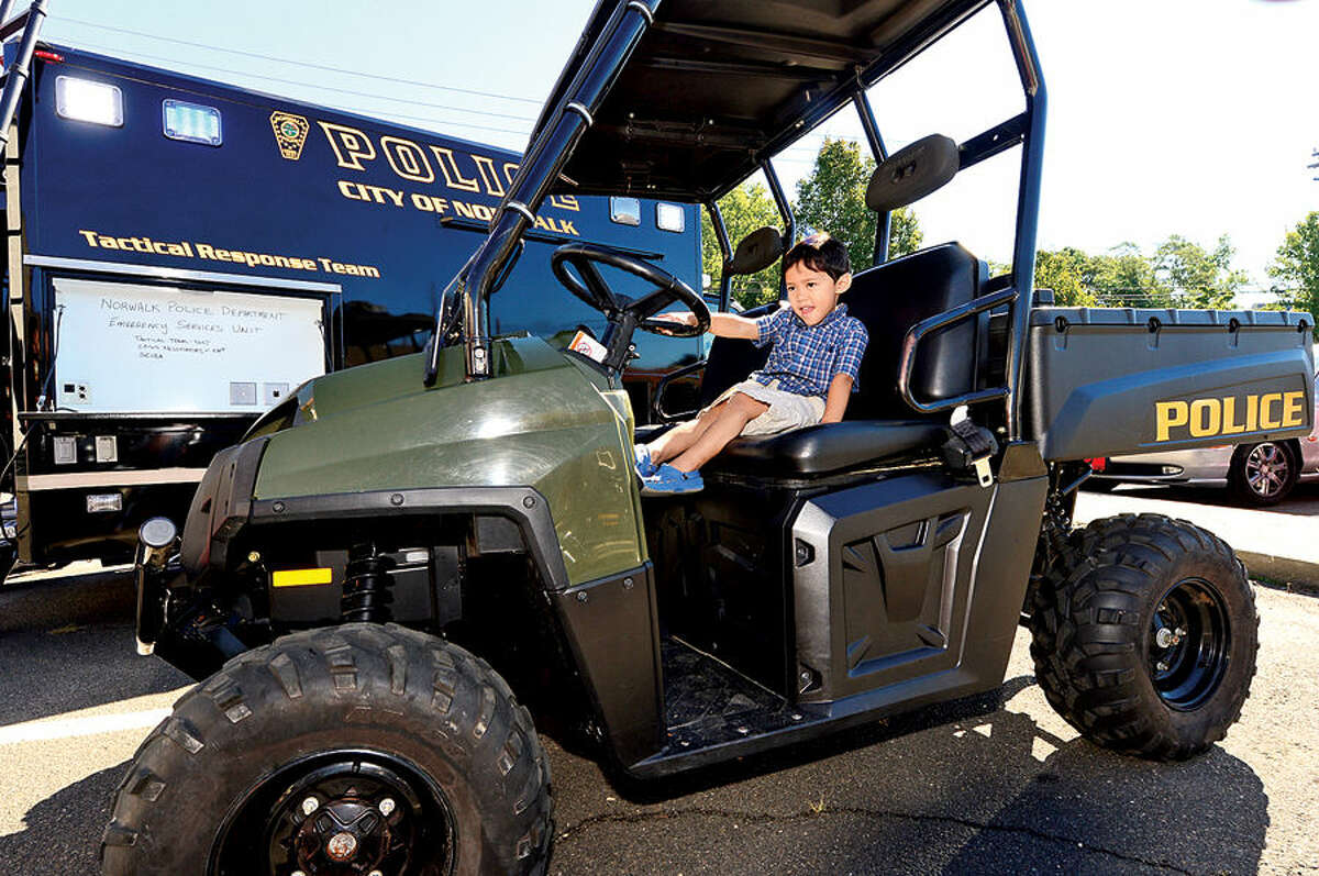 Hour photo / Erik Trautmann Gabriel Maranon, 3, pretends to drive a police ATV during The Norwalk Fire, Police and Public Works Departments' Open House and Touch- a- Truck on Saturday at the Public Works Center on South Smith Street. All three Departments will featured hands-on activities, give-aways and demonstrations for all ages.
