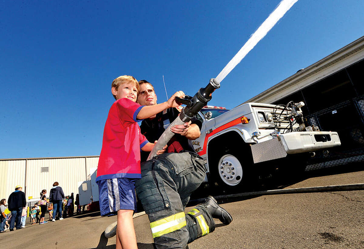 Hour photo / Erik Trautmann Matt Cesare, 6, sprays a fire hose with the help of firefighter Tony Bruno during The Norwalk Fire, Police and Public Works Departments' Open House and Touch- a- Truck on Saturday at the Public Works Center on South Smith Street. All three Departments will featured hands-on activities, give-aways and demonstrations for all ages.