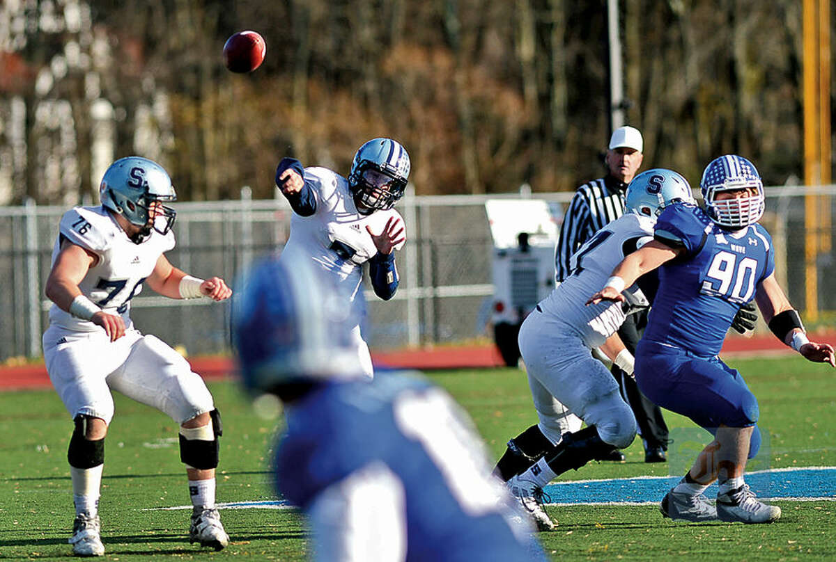 Hour photo / Erik Trautmann Quarterback for Staples, Andrew Speed tries to move the ball up field during a devastating defeat by Darien High School Saturday in Darien.