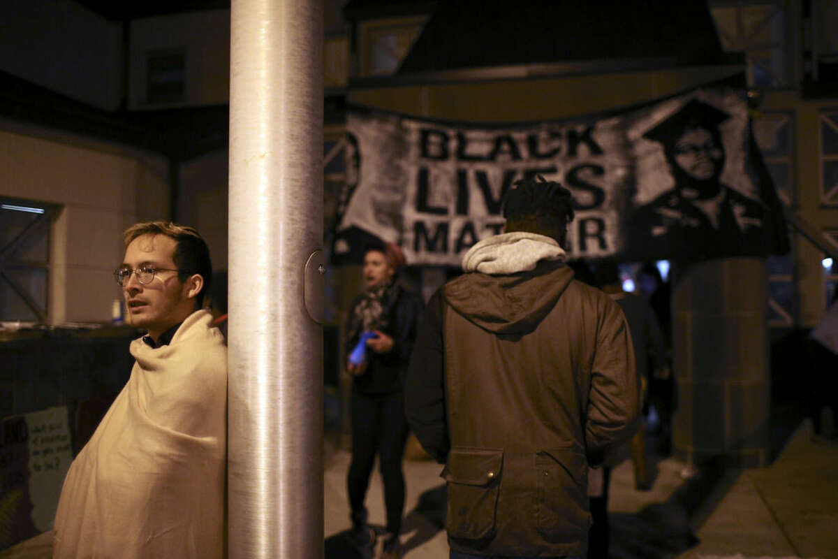 Protestors hung a banner over the front entrance to the 4th Precinct Station while several hunkered down in the entryway Sunday, Nov. 15, 2015, in Minneapolis, after a man was shot by Minneapolis police early Sunday morning. (Jeff Wheeler/Star Tribune via AP)