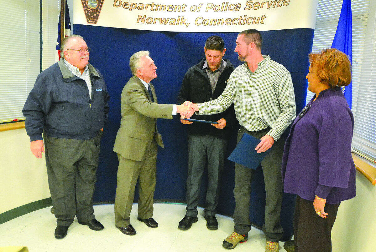 Hour Photo/Alex von Kleydorff The Norwalk Police Commission Mayor Harry Rilling, Charles Yost and Fran Collier Clemmons honor two employees from Eversource l-r William Evers and Craig Samatulski for their response at the scene of a fatal car accident in October
