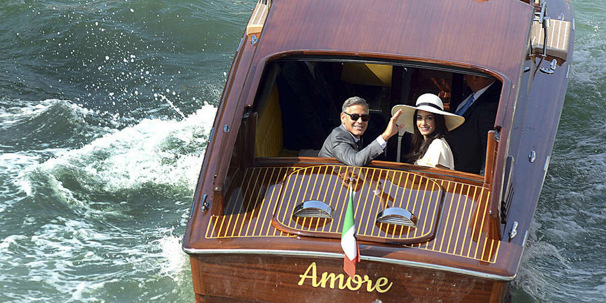 FOR USE AS DESIRED, YEAR END PHOTOS - FILE - George Clooney, flanked by his wife Amal Alamuddin, waves from a water-taxi after leaving the city hall in Venice, Italy, Monday, Sept. 29, 2014. George Clooney married human rights lawyer Amal Alamuddin, the actor's representative said, out of sight of pursuing paparazzi and adoring crowds. (AP Photo/Luigi Costantini)