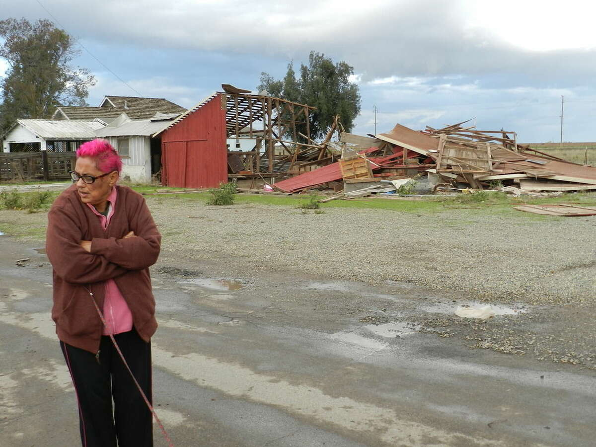 Sabina Woodard stands across the street from her destroyed barn after reports of a rare tornado in Denair, Calif., Sunday, Nov. 15, 2015. The National Weather Service said video and witness reports confirm a tornado touched down in Denair, which tore roofing and walls, knocked down trees and power lines and damaged gas lines. (Deke Farrow/The Modesto Bee via AP) LOCAL TELEVISION OUT (KXTV10, KCRA3, KOVR13, FOX40, KMAX31, KQCA58, CENTRAL VALLEY TV); LOCAL PRINT OUT (TURLOCK JOURNAL, CERES COURIER, OAKDALE LEADER, MODESTO VIEW, PATTERSON IRRIGATOR, MANTECA BULLETIN, RIPON, RECROD, SONORA UNION DEMOCRAT, AMADOR LEDGER DISPATCH, ESCALON TIMES, CALAVERAS ENTERPRISE, RIVERBANKS NEWS) LOCAL INTERNET OUT (TURLOCK CITY NEWS.COM, MOTHER LODE.COM); MANDATORY CREDIT
