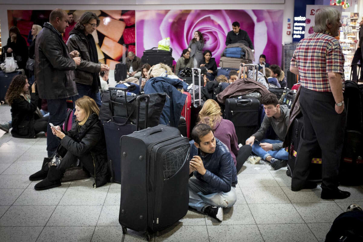 Travellers sit and wait at London's Gatwick Airport's North Terminal, Saturday Nov. 14, 2015, after the north terminal at Gatwick Airport was evacuated as a precaution after authorities found a suspicious article. Police described the evacuation Saturday as a precaution, but the incident comes at a time of heightened concern in Britain in the aftermath of the terror attacks in Paris. (Stefan Rousseau/PA via AP) UNITED KINGDOM OUT NO SALES NO ARCHIVE