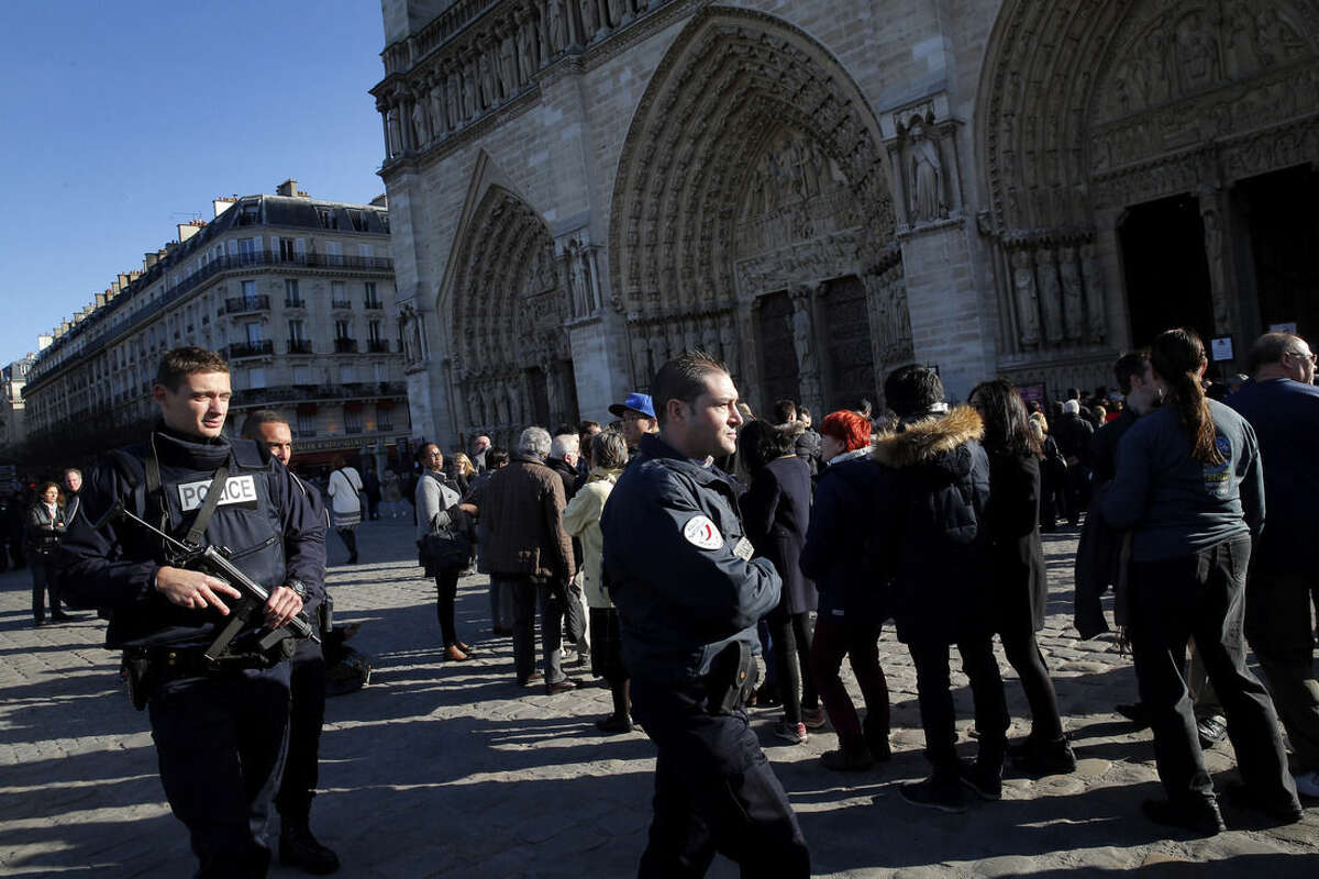 Policemen patrol in front of Notre Dame cathedral, following the Paris attacks, Sunday, Nov. 15, 2015. The Islamic State group claimed responsibility for Friday's attacks on a stadium, a concert hall and Paris cafes that left more than 120 people dead and over 350 wounded. (AP Photo/Christophe Ena)