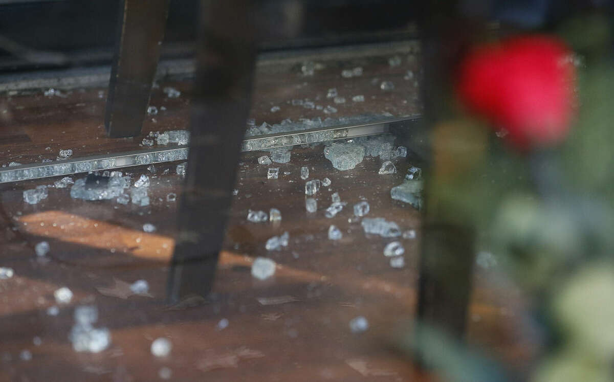 A rose leans on the window as broken glass is strewn across the floor inside the restaurant on Rue de Charonne, Paris, Sunday, Nov. 15, 2015, where attacks took place on Friday. The Islamic State group claimed responsibility for Friday's attacks on a stadium, a concert hall and Paris cafes that left more than 120 people dead and over 350 wounded. (AP Photo/Frank Augstein)