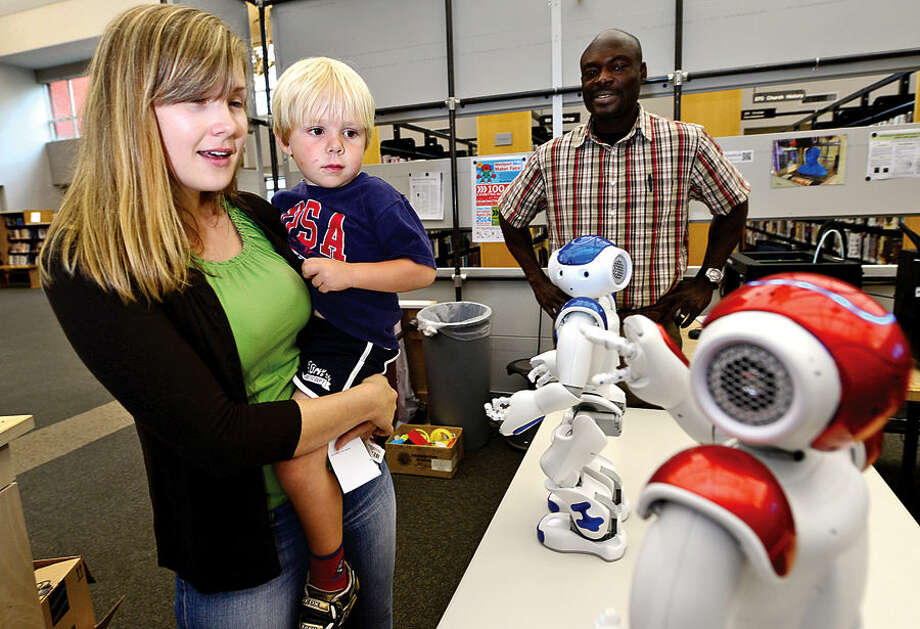 Hour photo / Erik Trautmann Kira Pantchenko and Tomas O'Byrne visit with the Westport Public Library newest acquisitions, two Aldebaran humanoid robots, Vincent and Nancy. The robots can be programmed to do a variety of tasks and will be available for the public to help learn coding and programming skills.