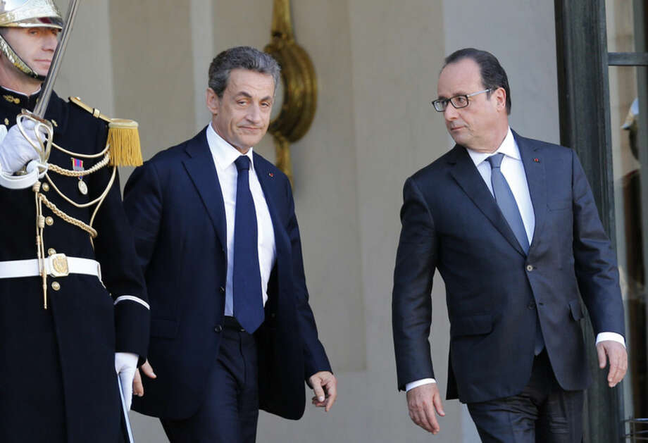 Former French President, Nicolas Sarkozy, leaves the Elysee Palace after a meeting with France's President, Francois Hollande, right, in Paris, Sunday, Nov. 15, 2015. French President Francois Hollande vowed to attack the Islamic State group without mercy as the jihadist group admitted responsibility Saturday for orchestrating the deadliest attacks inflicted on France since World War II. (AP Photo/Jacques Brinon)