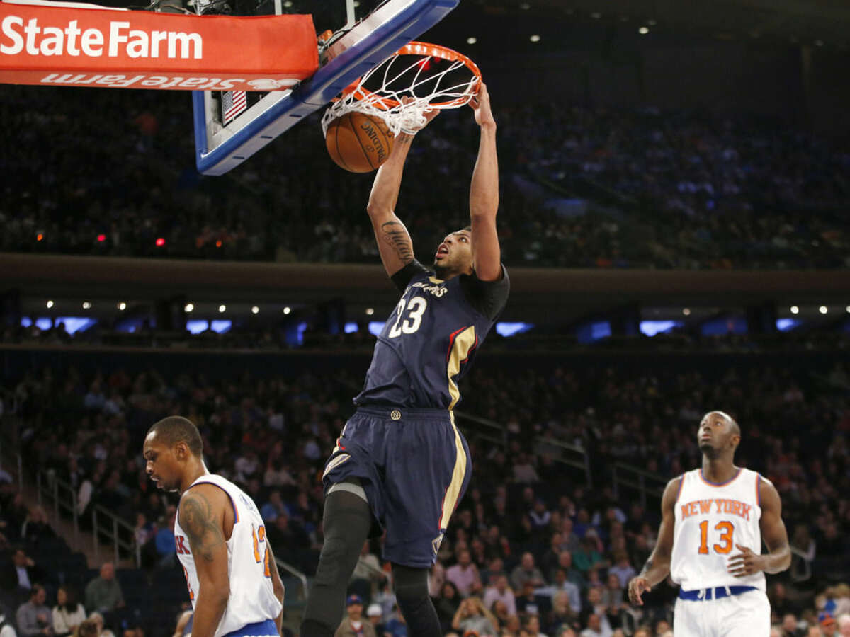 New Orleans Pelicans forward Anthony Davis (23) dunks with New York Knicks guard Jerian Grant (13) watching from the floor in the first half of an NBA basketball game at Madison Square Garden in New York, Sunday, Nov. 15, 2015. (AP Photo/Kathy Willens)