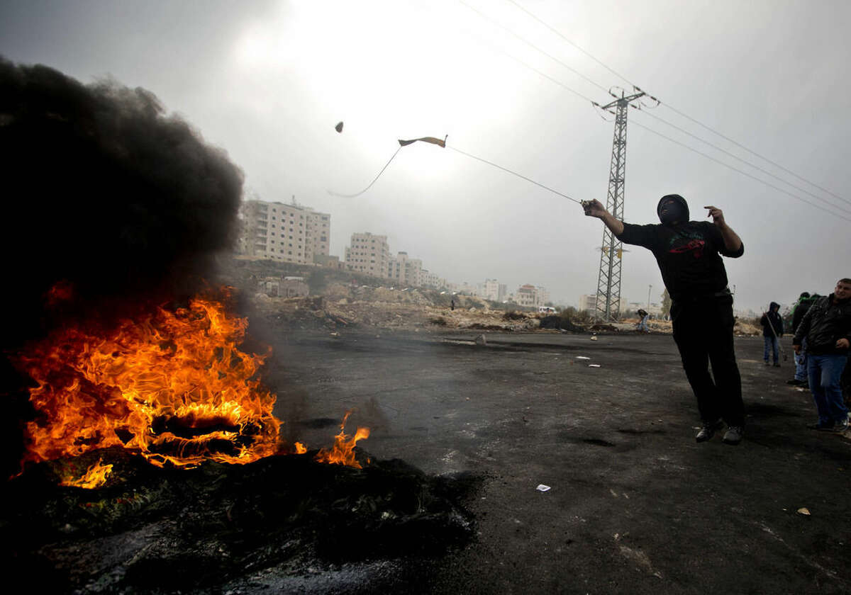 A Palestinian protester uses a sling shot to hurl stones at Israeli troops during clashes after the funerals of Ahmed Abu al-Aish, 28, and Laith Manasrah, 21, from Qalandia refugee camp, in the West Bank city of Ramallah, Monday, Nov. 16, 2015. Two Palestinians were killed and three wounded in clashes with Israeli troops early Monday in a Palestinian refugee camp in the Jerusalem area, a Palestinian health official said. (AP Photo/Majdi Mohammed)