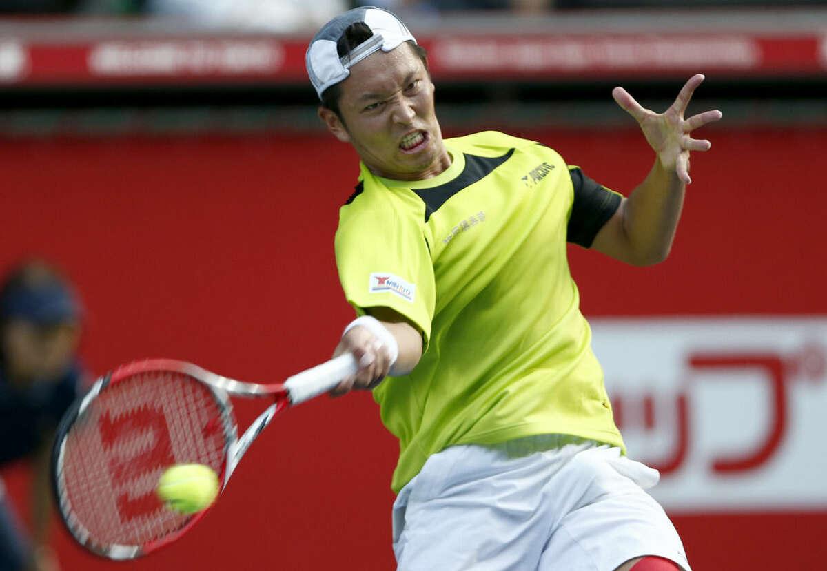 Tatsuma Ito of Japan returns a shot against Stanislas Wawrinka of Switzerland during their first round match of Japan Open Tennis Championships in Tokyo, Tuesday, Sept. 30, 2014. (AP Photo/Shizuo Kambayashi)