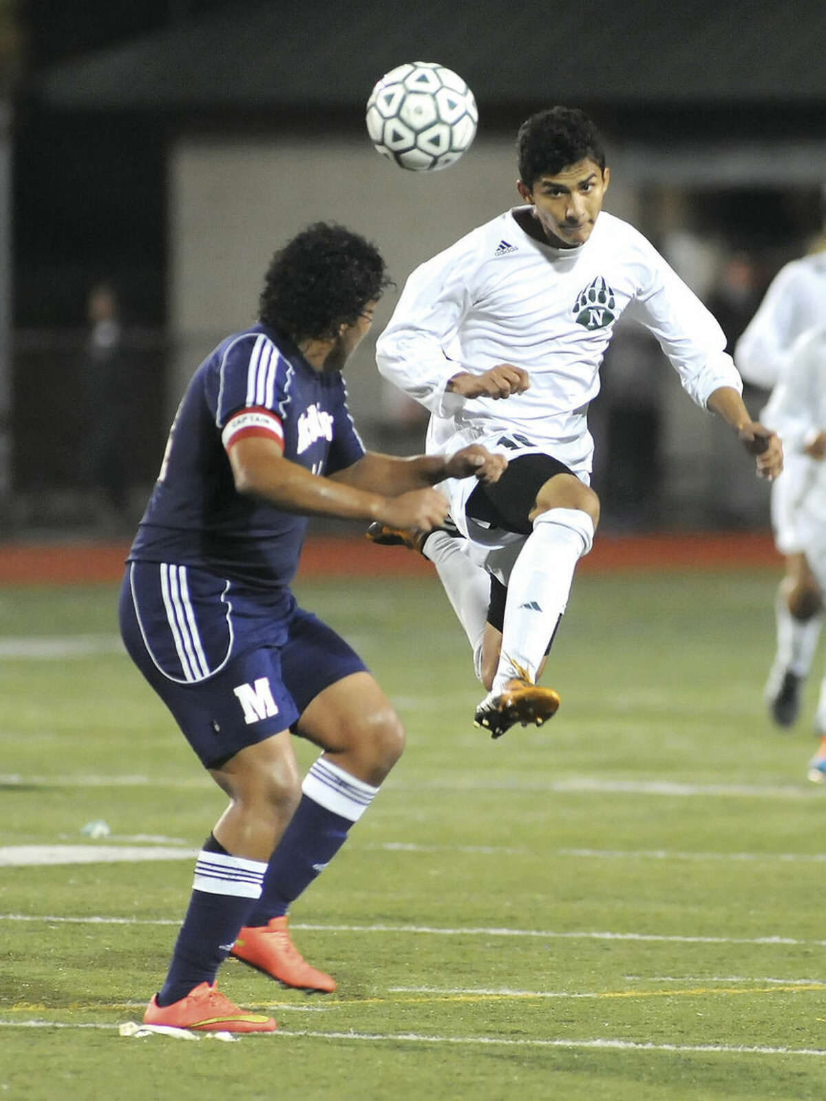 Hour photo/John Nash Norwalk's Patrick Barrantes, right, heads the ball past Brien McMahon's Sergio Ceja during Tuesday's game at Testa Field in Norwalk.