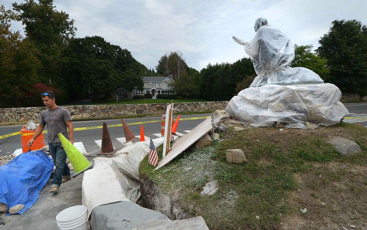 Hour Photo/Alex von Kleydorff The Minuteman statue is shrouded in plastic sheeting for protection as a crew from John Giunta General Contractos re builds the stone wall around him on So. Compo Rd in Westport