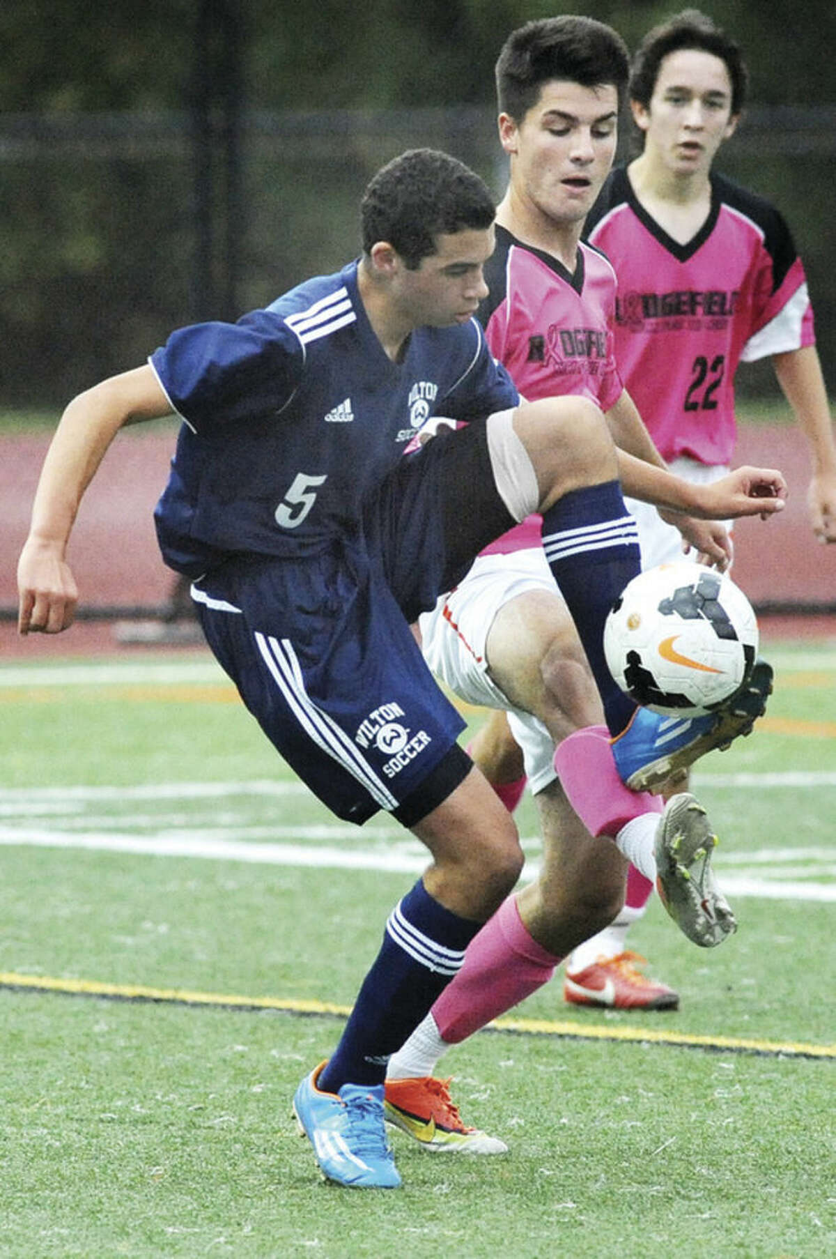 Hour photo/Matthew Vinci Wilton's Cole Hawthorne controls a ball, while Ridgefield's Andrew Papa sticks his foot in during Tuesday's game.