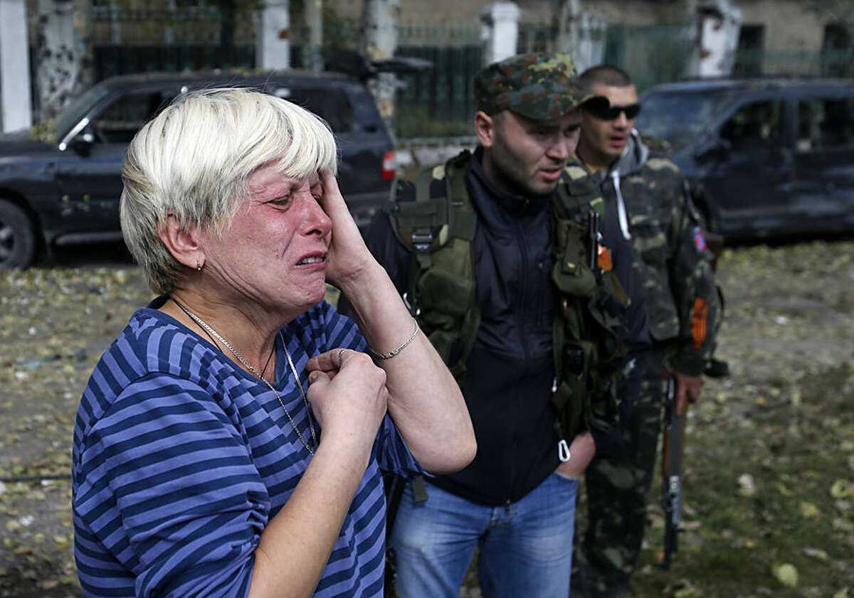 A local woman cries in front of a damaged school after shelling in the town of Donetsk, eastern Ukraine, Wednesday, Oct. 1, 2014. Rebels in eastern Ukraine appear to be successfully closing in on the government-held airport of Donetsk, a strategic victory for the pro-Russian separatists that further undermines a shaky cease-fire in the region. (AP Photo/Darko Vojinovic)
