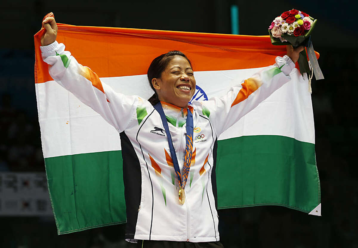India's M.C. Mary Kom holds the Indian national flag and celebrates her gold medal in the women's flyweight (48-51kg) final boxing match at the 17th Asian Games in Incheon, South Korea, Wednesday, Oct. 1, 2014. (AP Photo/Kin Cheung)